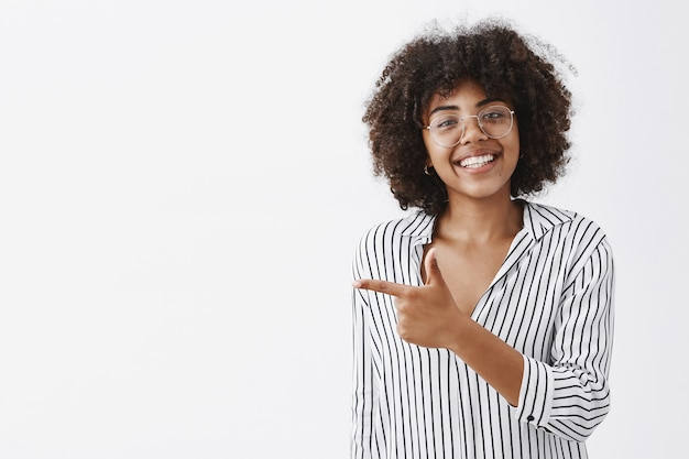Simpática e educada garota afro-americana bonita de óculos com cabelo encaracolado em blusa listrada de escritório apontando para a esquerda com uma arma de dedo e sorrindo de alegria dando conselhos aonde ir