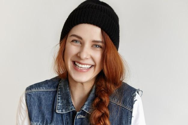 Simpática e encantadora garota caucasiana com cabelo ruivo trançado e rindo alegremente