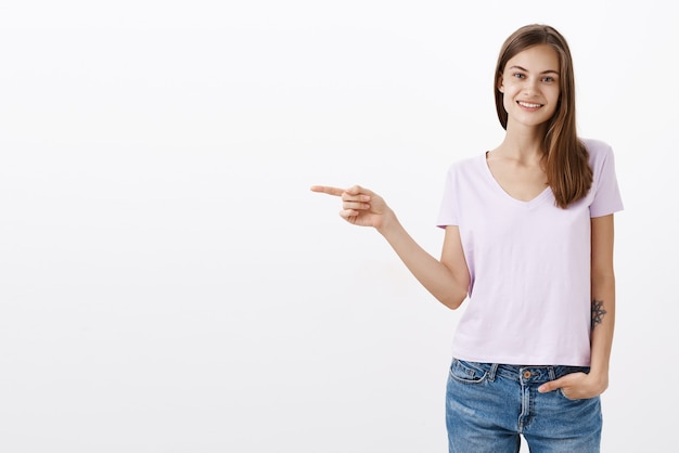 Simpática e encantadora mulher morena em blusa e jeans jeans segurando a mão no bolso sorrindo despreocupada e relaxada apontando para a direita mostrando a direção ou oferecendo uma visita em um lugar agradável sobre uma parede branca