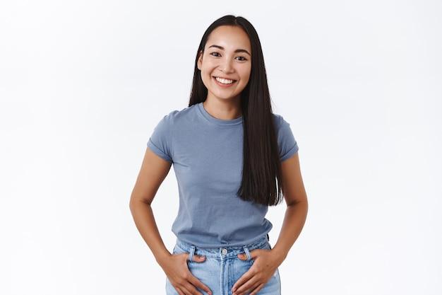 Simpática e simpática terna morena asiática em t-shirt, de mãos dadas nos bolsos da calça jeans, rindo e sorrindo encantada, conversando com a garota durante o encontro no clube lgbt, parecendo modesta e bonita