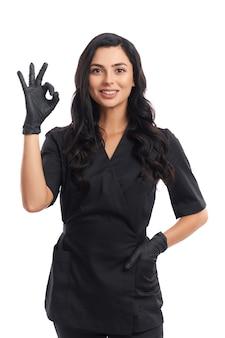 Simpática médica de uniforme preto e luvas, mostrando sinal de ok com os dedos