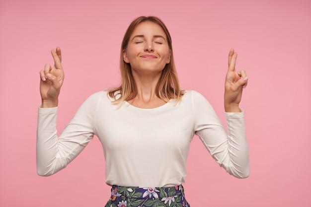 Simpática senhora loira bonita posando sobre um fundo rosa com os olhos fechados e sorrindo esperançosamente, cruzando os dedos para dar sorte, vestindo blusa branca e saia florida