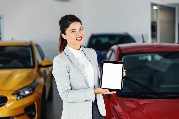 Simpática, sorridente concessionária de automóveis em pé no salão de automóveis e mostrando a tela do tablet.