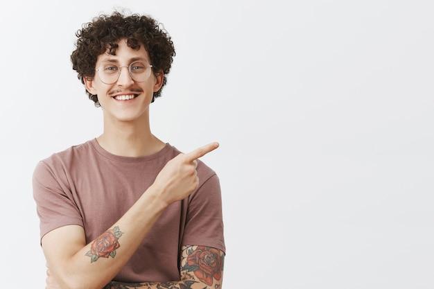 Simpático, bonito e criativo, jovem e elegante modelo masculino com tatuagens de penteado encaracolado e bigode sorrindo alegremente apontando para o canto superior direito