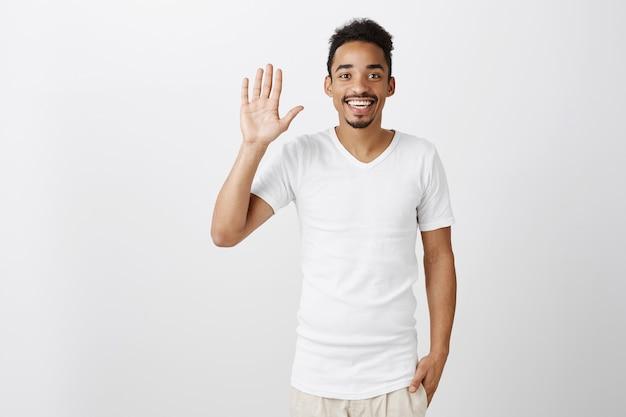 Simpático cara de pele escura acenando com a mão, dizendo olá, cumprimentando ou dando as boas-vindas a pessoa, sorrindo alegre