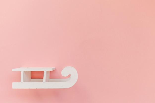 Simples composição mínima trenó branco isolado em fundo rosa pastel