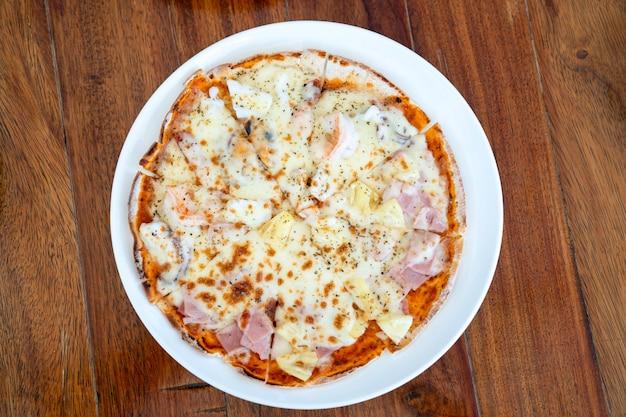Simples e básico normal, círculo completo de solado pizza em prato branco na mesa de madeira
