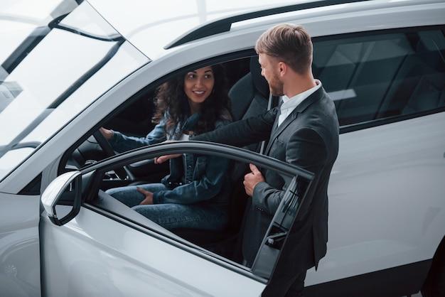 Simples e confortável. cliente do sexo feminino e empresário barbudo elegante e moderno no salão automóvel