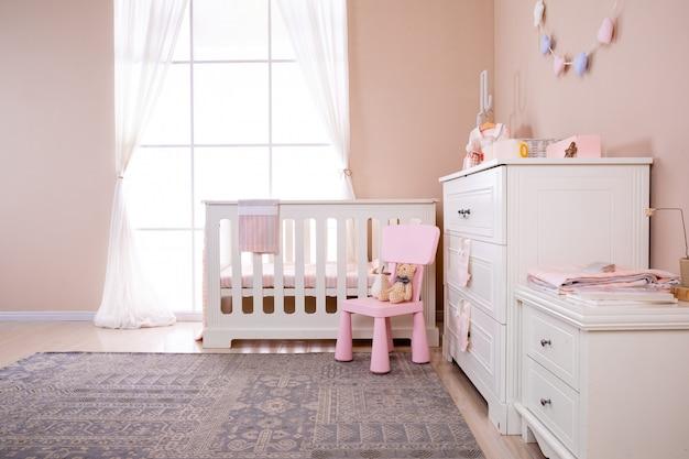 Simples, quarto de bebê branco com berço e tapete