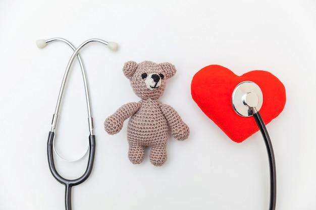 Simplesmente design minimalista brinquedo urso vermelho coração e medicina equipamento estetoscópio isolado