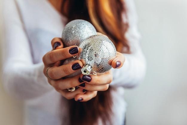 Simplesmente design minimalista mulher feminina mão segurando uma bola de prata de enfeite de natal isolada