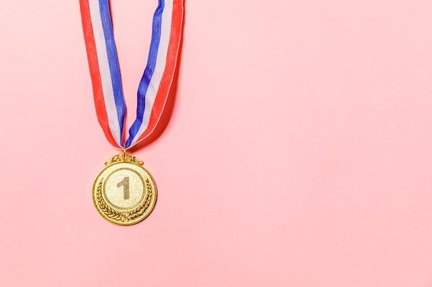 Simplesmente plana leigos vencedor do projeto ou medalha do troféu de ouro do campeão isolada no fundo colorido rosa. vitória em primeiro lugar de competição. conceito de vitória ou sucesso. espaço da cópia da vista superior.