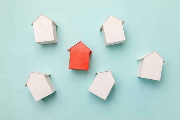 Simplesmente plano leigo design com casa modelo de brinquedo vermelho em miniatura entre casas brancas isoladas em fundo azul pastel. indústria imobiliária. conceito de escolha de bairro exclusivo de comunidade.