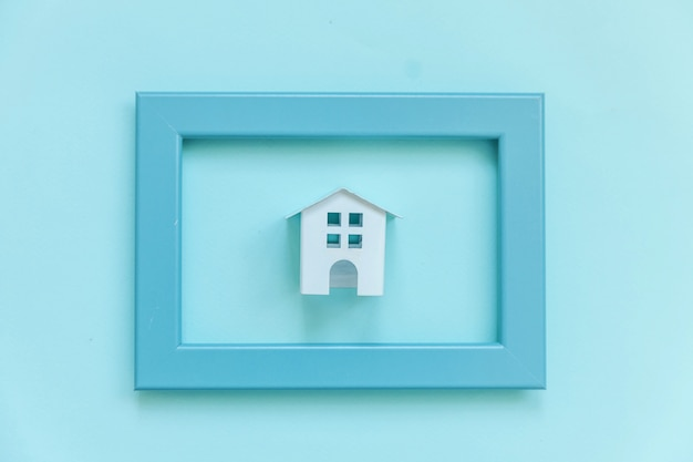Simplesmente projete com casa de brinquedo branco em miniatura no quadro azul isolado no fundo azul colorido pastel moderno