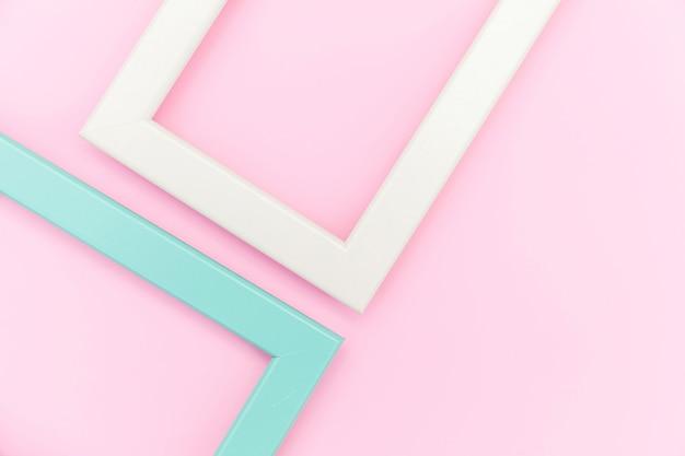 Simplesmente projete com moldura rosa e azul vazia isolada no fundo colorido pastel rosa