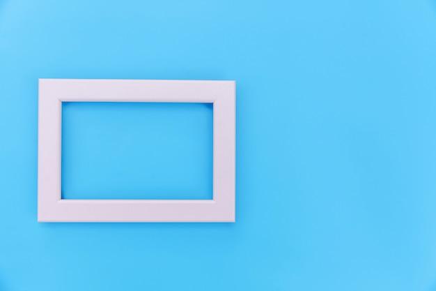 Simplesmente projete com moldura rosa vazia, isolada no fundo colorido pastel azul. vista superior, plana leigos, cópia espaço, mock-se. conceito mínimo.