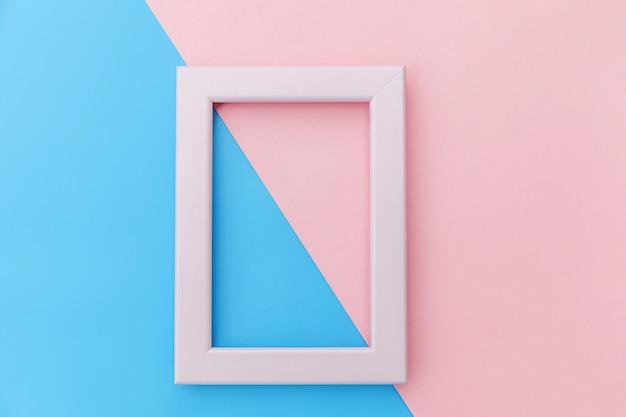 Simplesmente projete com moldura rosa vazia, isolada no fundo colorido pastel rosa e azul