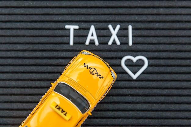 Simplesmente projete o modelo de táxi de carro de brinquedo amarelo com palavra de letras taxi de inscrição