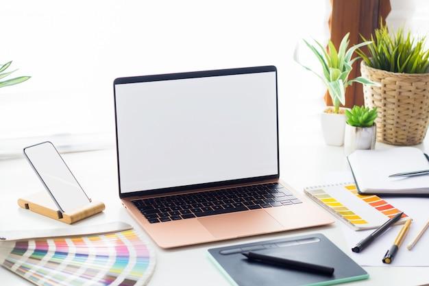 Simulação de laptop e telefone no espaço de trabalho do designer gráfico