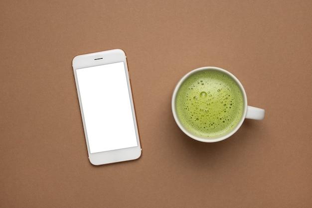 Simulação de telefone celular e chá verde quente tarde com estilo moderno e delicioso em fundo marrom claro, vista superior macro de textura matcha