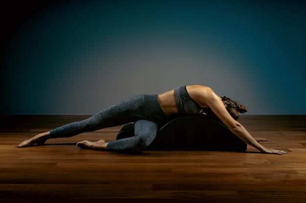 Simulador reformador, a menina treinadora de pilates faz exercícios de alongamento e modelagem da postura correta