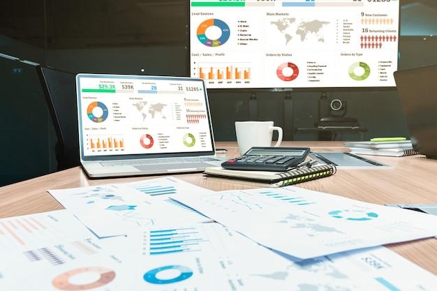 Simule a apresentação de slides de resumo de vendas no laptop de exibição com calculadora e papelada na mesa na reunião