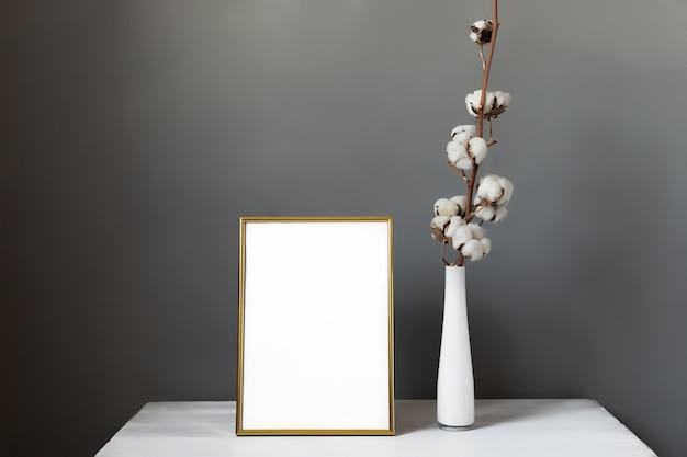 Simule a moldura e o vaso com raminhos de algodão no fundo cinza da parede