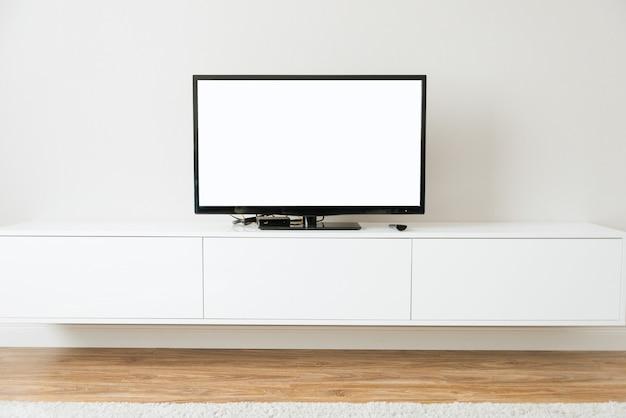 Simule a smart tv com tela branca em pé na sala de estar branca
