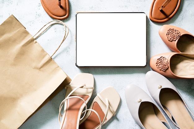 Simule a tela do tablet digital em branco em acessórios elegantes de moda bege com