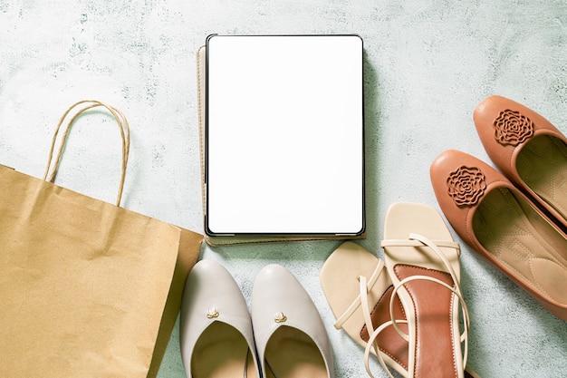 Simule a tela do tablet digital em branco em acessórios elegantes de moda bege