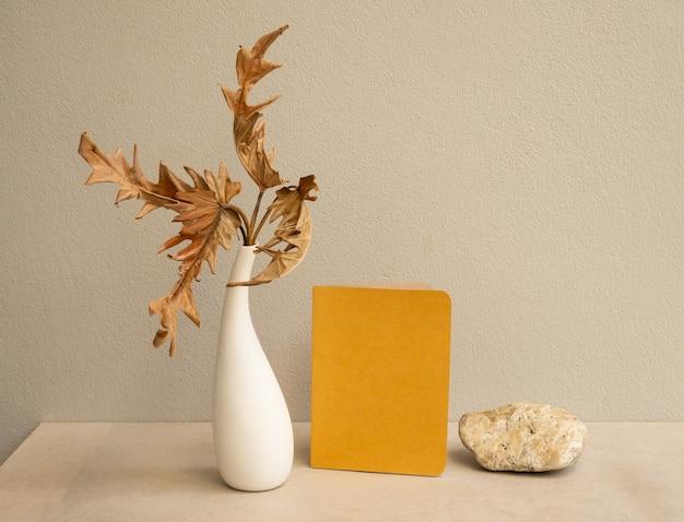 Simule cartões de convite marrons e folhas secas de filodendro exóticas em um vaso moderno