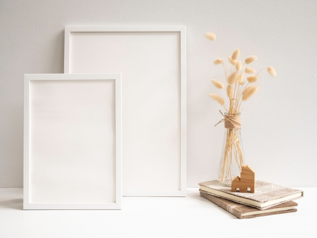 Simule duas molduras de pôster, crie um livro e uma composição de flores secas de lagurus ovatus em um vaso de vidro moderno na mesa branca e na superfície da parede de cimento