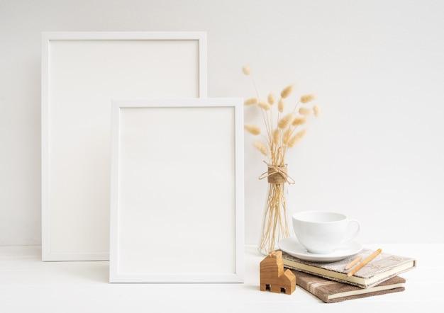 Simule duas molduras de pôster, xícara de café, livro de jangada, modelo de casa e flores secas de lagurus ovatus