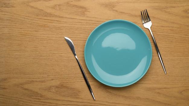Simule o prato de cerâmica, o garfo e a faca de mesa na mesa de madeira, vista superior, prato limpo, prato de cerâmica vazio, plano de fundo da mesa