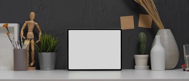 Simule o tablet em uma mesa de trabalho moderna com pincéis de pintura e decorações