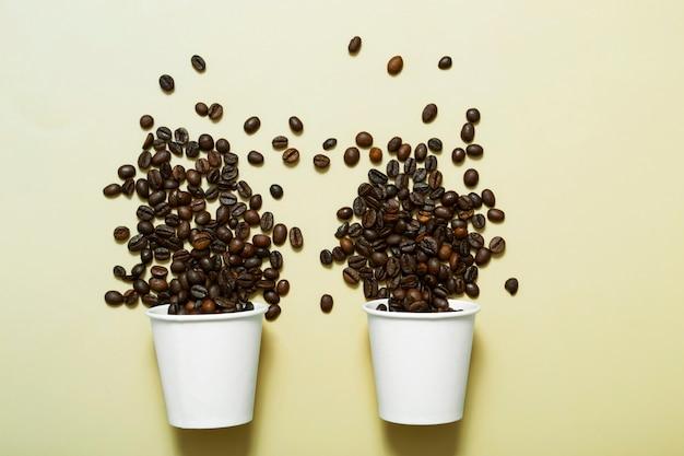 Simule um copo de papel branco com grãos de café em um fundo bege dois copos de papel