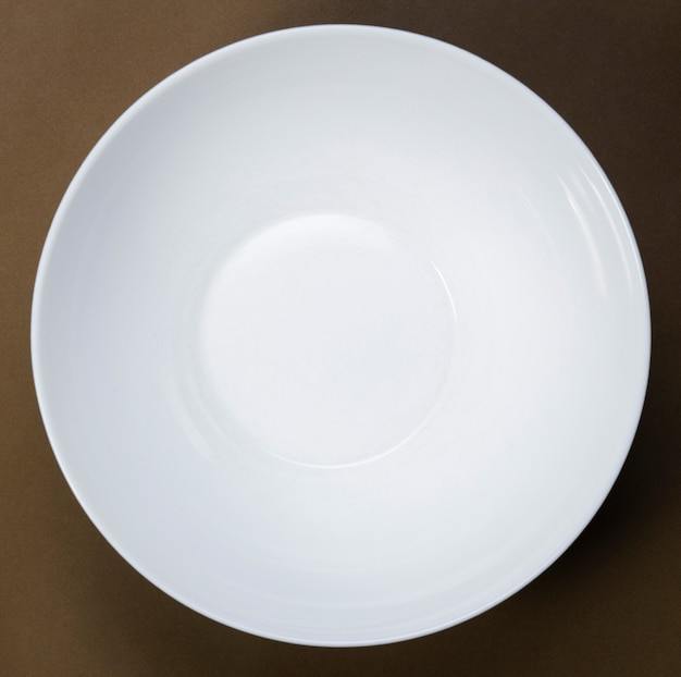 Simule um prato branco profundo vazio no espaço amarelo, vista superior