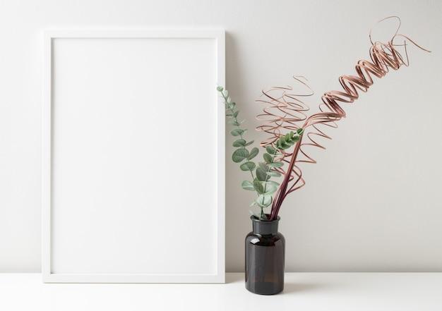 Simule uma moldura de pôster branca com folhas de eucalipto e galhos secos em um vaso de vidro marrom na superfície branca