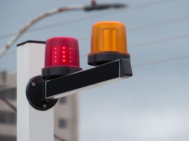 Sinais de aviso de saída de veículos com luz vermelha e amarela.