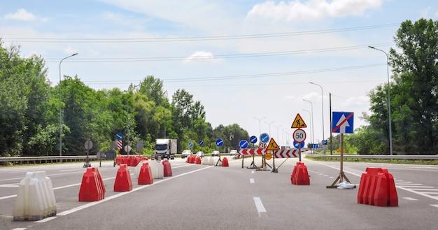 Sinais de aviso em uma seção perigosa da estrada mostrando as direções de tráfego. obras rodoviárias