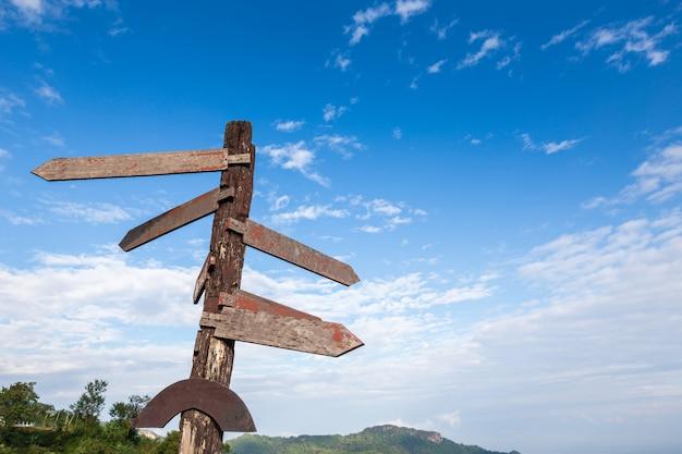 Sinais de forma de seta de madeira em branco contra o céu azul, sinais de direção de madeira velha contra o azul sk