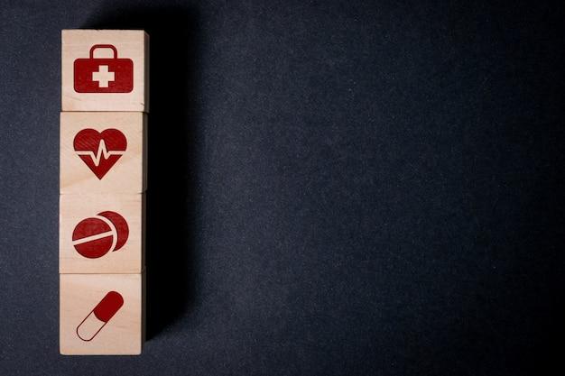Sinais de medicina, coração, comprimidos e cápsulas em cubos de madeira em um fundo preto. copie o espaço.