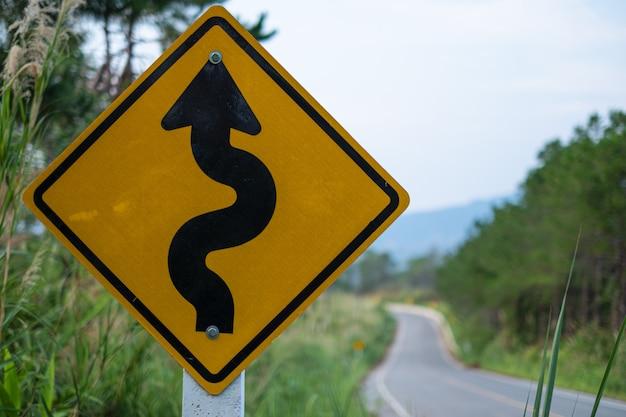 Sinais de trânsito amarelo aviso contra estrada sinuosa em frente na grama verde