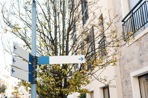 Sinais de trânsito em branco pendurados em um poste na rua perto de um prédio na cidade