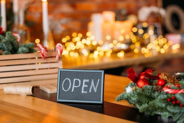 Sinal aberto. quadro com palavra aberta sobre desfocar interior festivo.