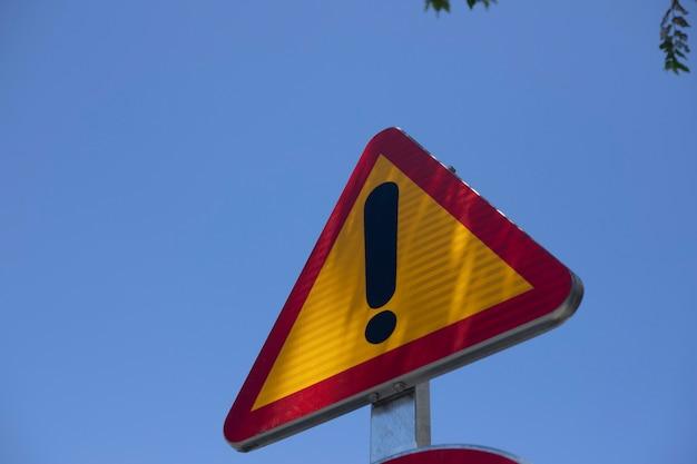 Sinal ao ar livre com ponto de exclamação. sinal de cuidado ao ar livre.