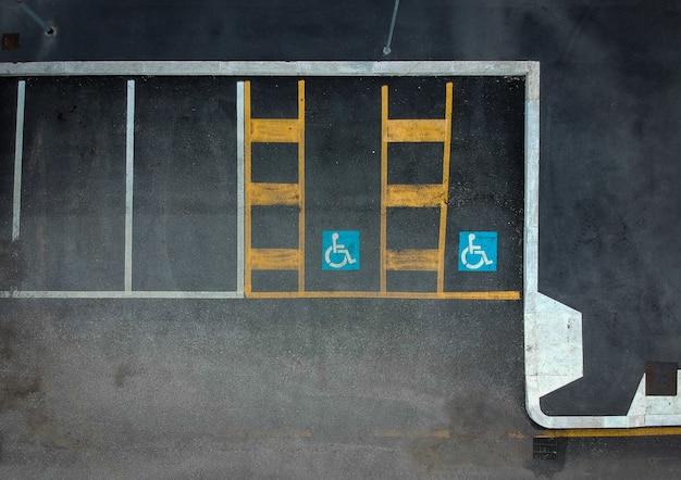 Sinal azul incapacitado do estacionamento pintado no asfalto escuro. espaços deficientes deficientes no preto.