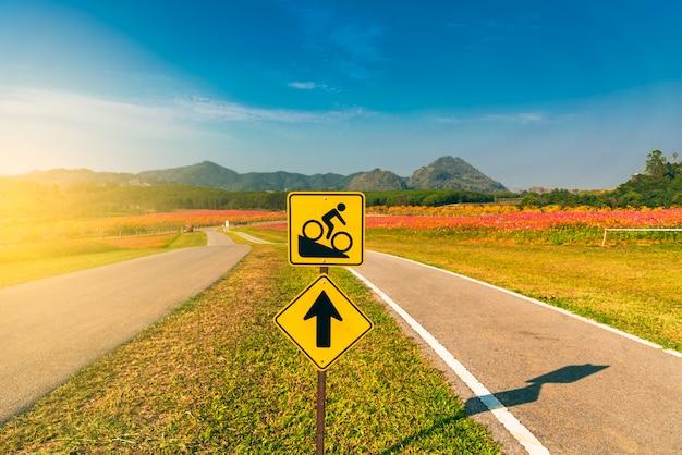 Sinal da bicicleta à estrada íngreme com fundo da cordilheira e do céu azul.