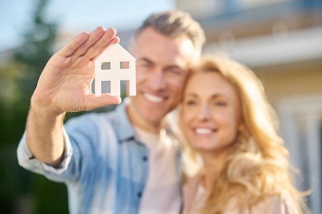 Sinal da casa na mão do homem abraçando a esposa