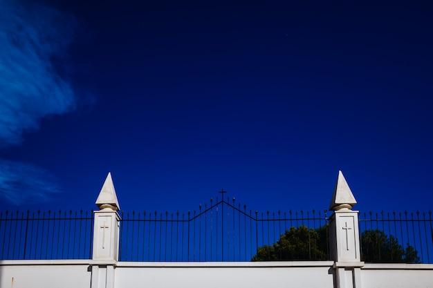 Sinal da cruz gravada nas paredes brancas de um cemitério, conceito de isolamento religioso.
